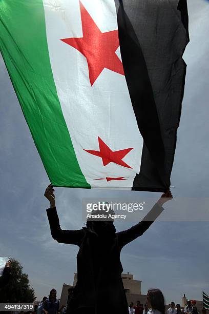 Syrian opponents living in Jordan hold national flags during a protest against the Syrian presidential elections outside the Syrian Embassy in Amman...