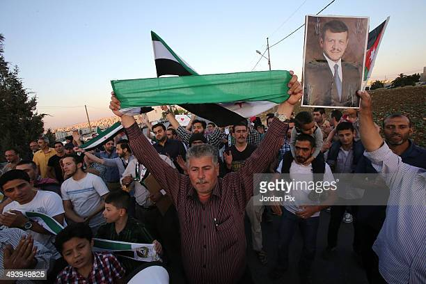 Syrian opposition activists hold up a portrait of Jordan's King Abdullah II durng a rally in support of the expelling of the Syrian ambassador to...