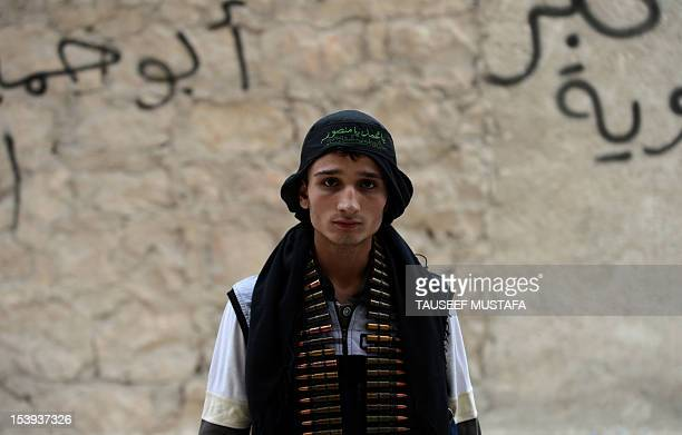 A Syrian opposition fighter stands near a post in the northern Syrian city of Aleppo on October 11 2012 Rebels cut off the highway linking Damascus...