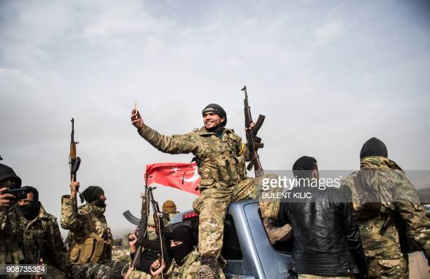 Syrian opposition fighter takes a selfie as fighters walk through Syria in front of Turkish troops near the Syrian border at Hassa Hatay province on...