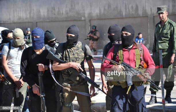 Syrian opposition fighters arrive at a checkpoint manned by regime forces ahead of their evacuation from the Waer neighbourhood the last...