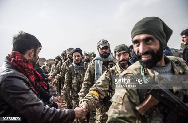 TOPSHOT Syrian opposition fighters walk through Syria in front of Turkish troops near the Syrian border at Hassa Hatay province on January 22 2018...