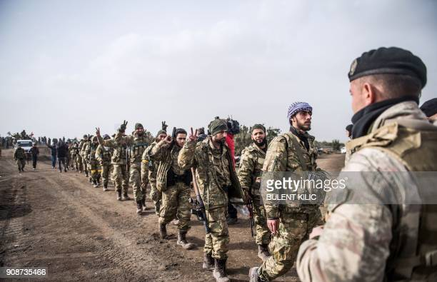 Syrian opposition fighters walk through Syria in front of Turkish troops near the Syrian border at Hassa Hatay province on January 22 2018 Turkey on...