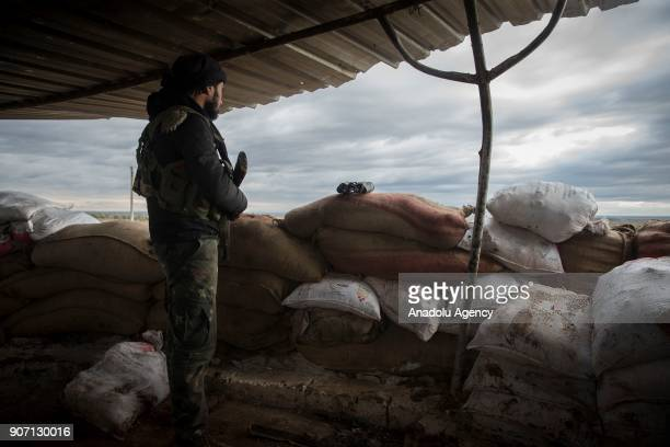 Syrian opposition member holds his gun as he keep guard on a bulwark to take action in the nearby city of Afrin for expected Afrin operation against...