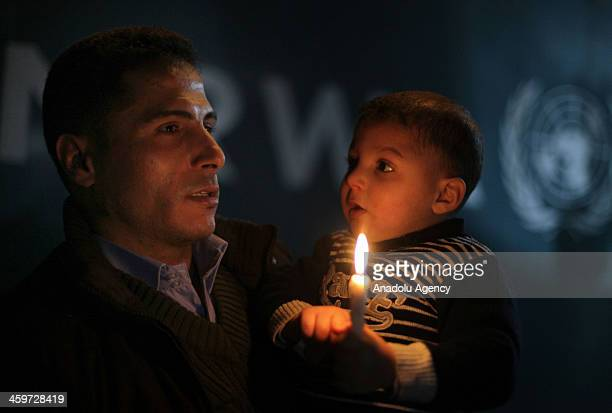 Syrian origin of Palestinian with his kid hold a candle in a protest to show his support to the people living in Yarmouk Palestinian refugee camp on...