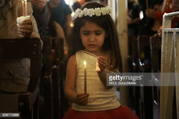 Syrian Orthodox Christian girl attends a mass in the divided northeastern city of Qamishli during Orthodox Easter celebrations on May 1, 2016....