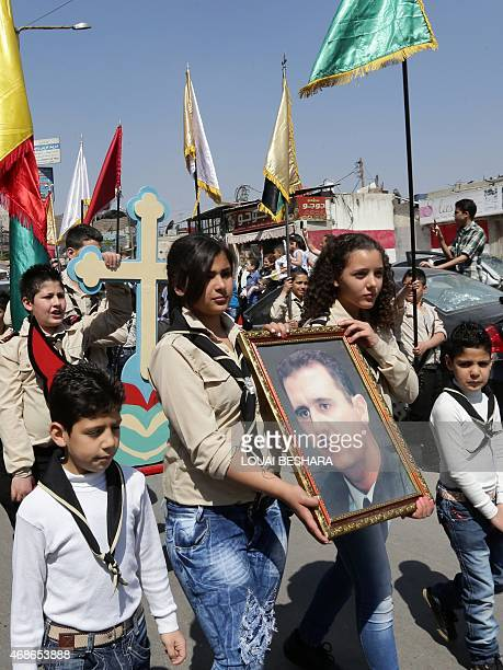Syrian Orthodox Christians carry a portrait of their President Bashar alAssad during the Palm Sunday procession on April 5 2015 in the Syrian capital...
