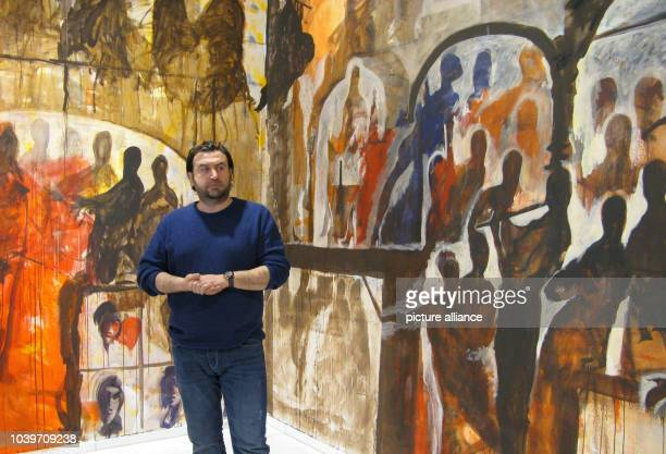 Syrian painter Khaled AlKhani stands in front of his painting 'The Beginning' in the Kunsthalle in Kiel Germany 14 March 2013 The artist covered the...