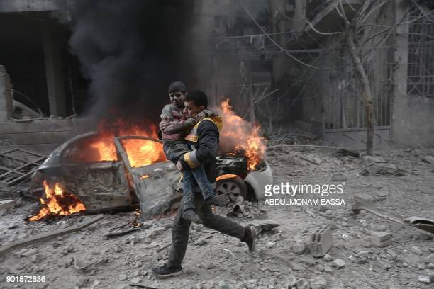 Syrian paramedic carries an injured child following reported bombardment by Syrian and Russian forces in the rebelheld town of Hamouria in the...