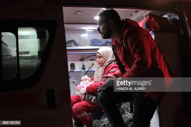 A Syrian paramedic holds a baby inside an ambulance on the second night of an evacuation operation led by the Syrian Red Crescent and the...