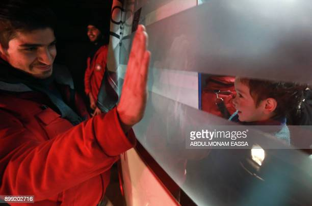A Syrian paramedic waves to children inside an ambulance on the second night of an evacuation operation led by the Syrian Red Crescent and the...