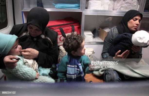 Syrian paramedics and civilians sit inside an ambulance on the second night of an evacuation operation led by the Syrian Red Crescent and the...