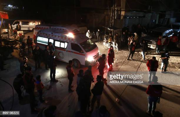 Syrian paramedics and civilians stand near an ambulance on the second night of an evacuation operation led by the Syrian Red Crescent and the...