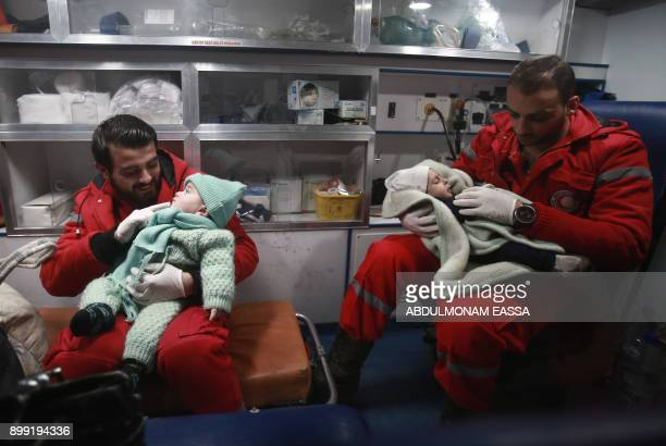 TOPSHOT Syrian paramedics distract children inside an ambulance on the second night of an evacuation operation led by the Syrian Red Crescent and the...