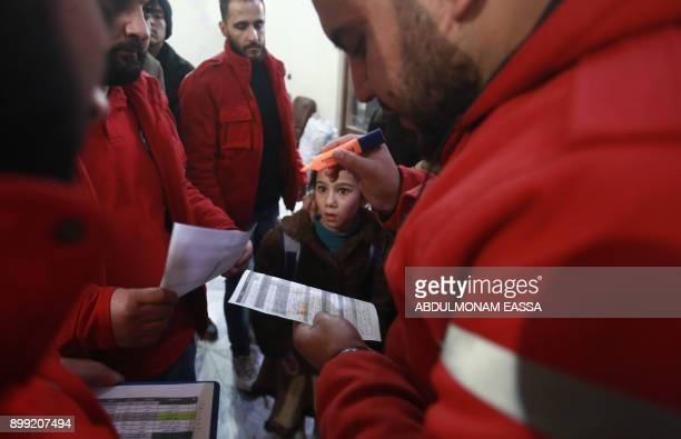 Syrian paramedics take notes on the second night of an evacuation operation led by the Syrian Red Crescent and the International Committee of the Red...