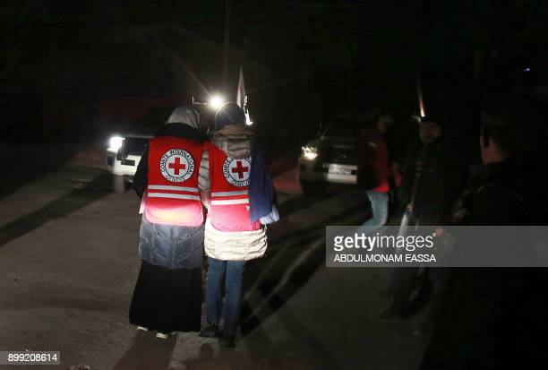Syrian paramedics take part in an evacuation operation led by Syria's Red Crescent and the International Committee of the Red Cross in Douma in the...