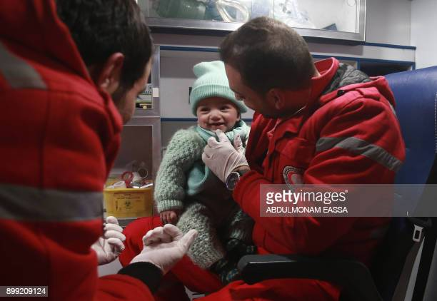 Syrian paramedics tend to a baby inside an ambulance on the second night of an evacuation operation led by the Syrian Red Crescent and the...