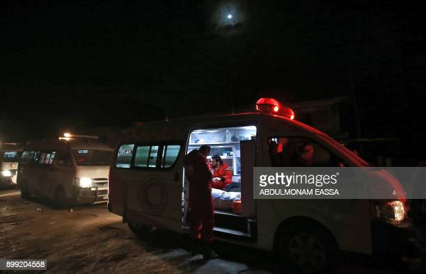 Syrian paramedics wait by an ambulance on the second night of an evacuation operation led by Syria's Red Crescent and the International Committee of...