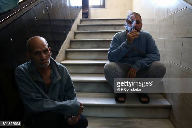 A Syrian patient smokes a cigarette as he sits on a staircase with another at a mental health clinic the sole such facility in the rebelheld north of...