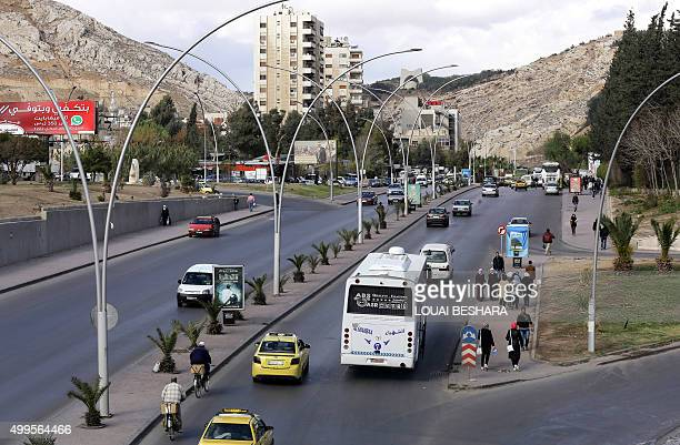 Syrian pedestrians and commuters are seen at Mazzeh highway in Damascus on December 2 2015 AFP PHOTO LOUAI BESHARA / AFP / LOUAI BESHARA