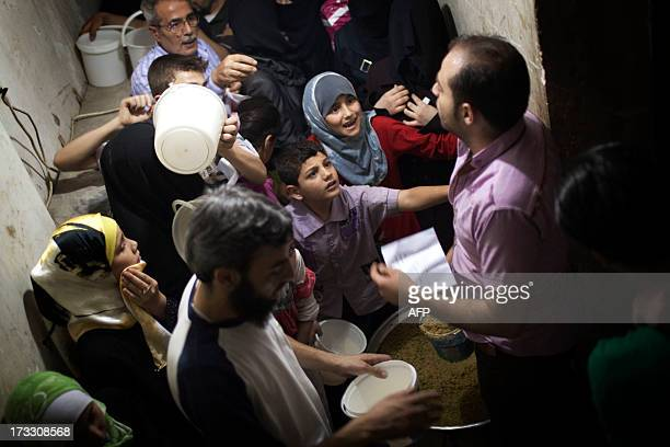Syrian people are given an Iftar meal during the second day of the Muslim holy month of Ramadan in the Bustan alQasr district of Aleppo on July 11...