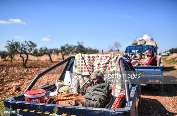 TOPSHOT Syrian people arrive at a check point in the village of Anab ahead of crossing to the Turkishbacked Syrian rebels side on March 17 as...