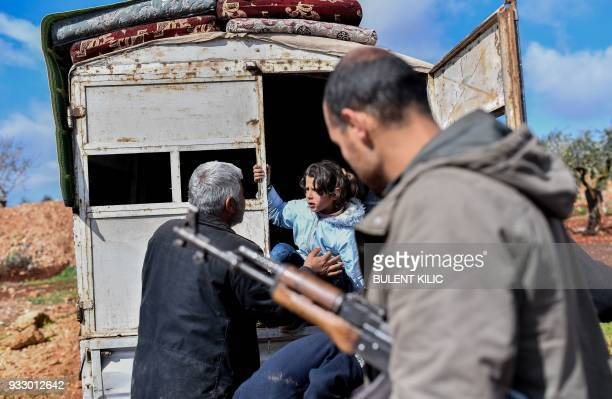 Syrian people arrive at a check point in the village of Anab ahead of crossing to the Turkishbacked Syrian rebels side on March 17 as civilians flee...