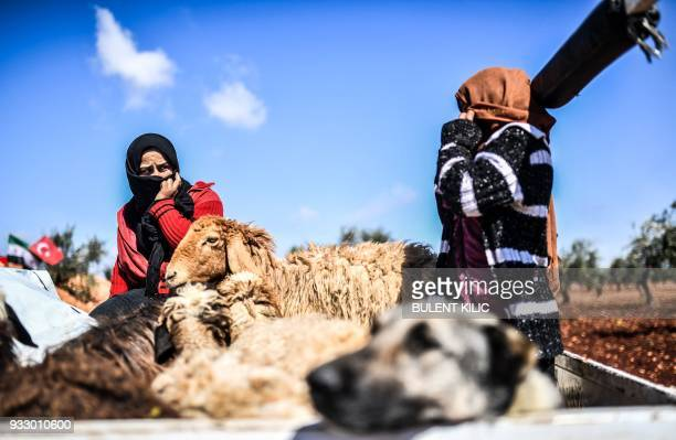 Syrian people arrive at a check point with livestock in the village of Anab ahead of crossing to the Turkishbacked Syrian rebels side on March 17 as...
