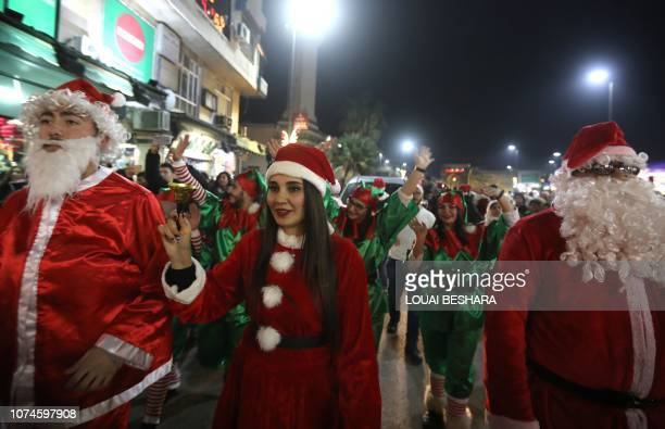 Syrian people dressed as Santa Claus walk in the capital Damascus' central neighbourhood of Qassaa to celebrate Christmas early on December 22 2018