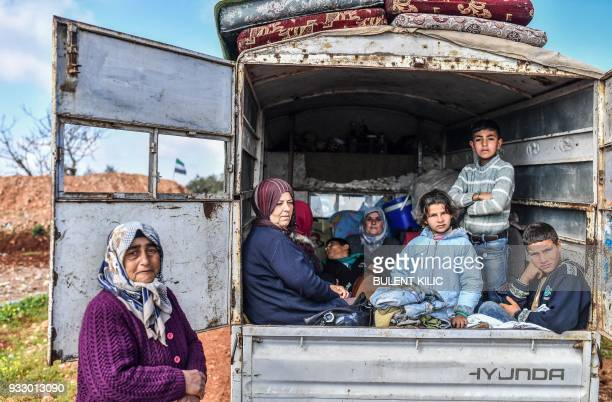 TOPSHOT Syrian people look on as they arrive at a check point in the village of Anab ahead of crossing to the Turkishbacked Syrian rebels side on...