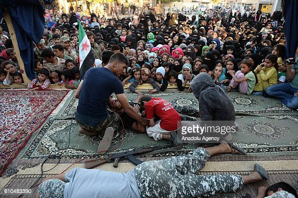 Syrian people perform a theatre play on a stage which is set at the city centre after the cleansing of Daesh in Jarabulus Syria on September 25 2016...