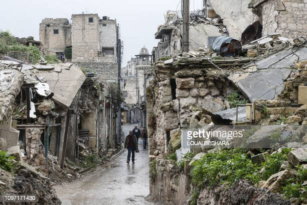 TOPSHOT Syrian people walk amid destruction in the Bab alQinnasrin area in Aleppo's Old city on February 10 2019