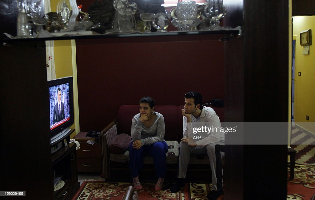 Syrian people watch Syria's embattled President Bashar al-Assad making a public address on the state-run Syrian TV, on January 6, 2013 in Damascus. Bashar al-Assad in a rare speech Sunday denounced the opposition as 'slaves' of the West and called for a national dialogue conference to be followed by a referendum on a national charter and parliamentary elections.