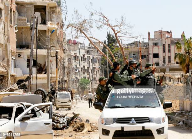 TOPSHOT Syrian police flash the sign for victory in the back of a vehicle as they drive down a destroyed street in Douma on the outskirts of Damascus...