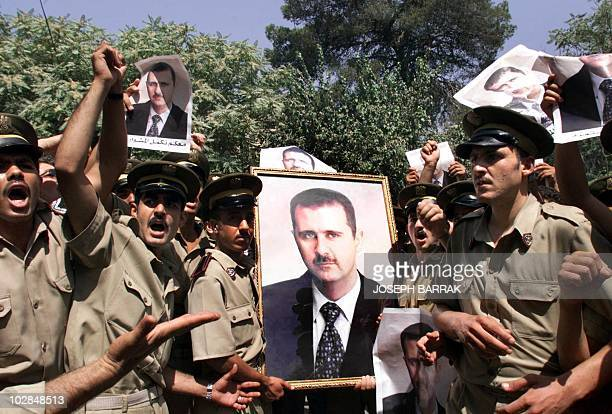 Syrian policemen carry pictures of Bashar alAssad outside a polling station in Damascus 10 July 2000 as Syrians go to the polls in a plebiscite to...