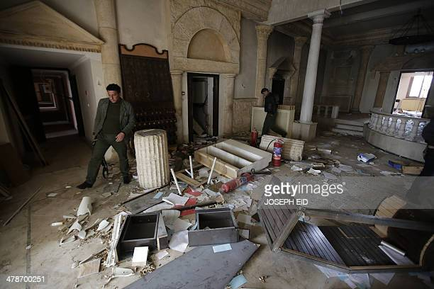 Syrian policemen walk inside the ransacked Sham Zenobia Palace Hotel which is situated opposite the ruins of the ancient city of Palmyra 215...