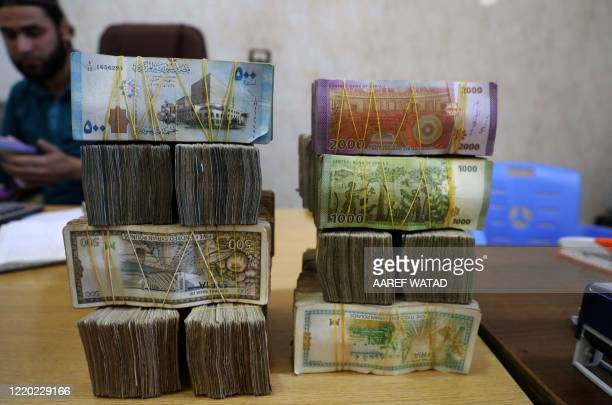 Syrian pounds are pictured at a currency exchange shop in the town of Sarmada in Syria's northwestern Idlib province, on June 15, 2020. - Authorities...