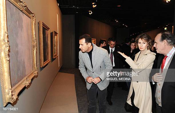 Syrian President Bashar alAssad his wife Asma and French Culture Minister Frederic Mitterrand look at a painting as they visit the exhibition...