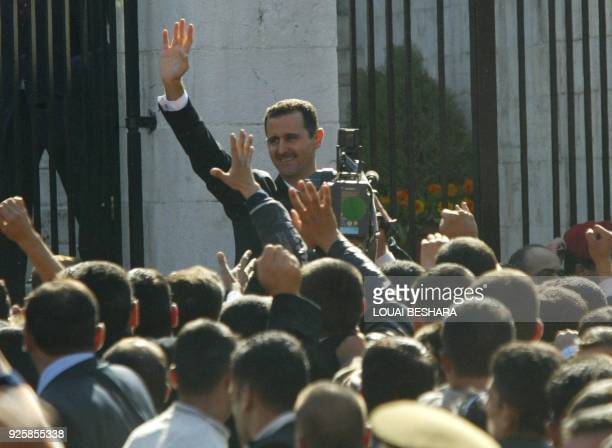 Syrian President Bashar alAssad salutes demonstrators who gathered in support of him after delivering a speech at Damascus University 10 November...