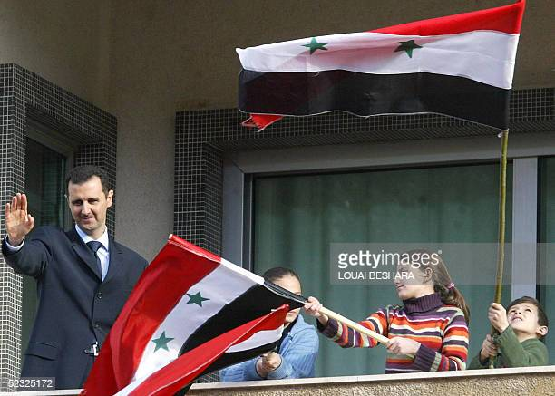 Syrian President Bashar alAssad salutes the crowd as children wave their national flag during a demonstration in Damascus 09 March 2005 Tens of...