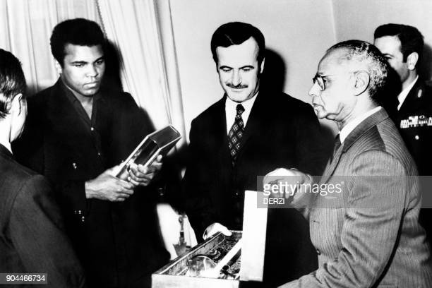Syrian President Hafez elAssad offers a sword and the koran to US boxing heavyweight champion Muhammad Ali in Damas on January 20 1972 / AFP PHOTO /...