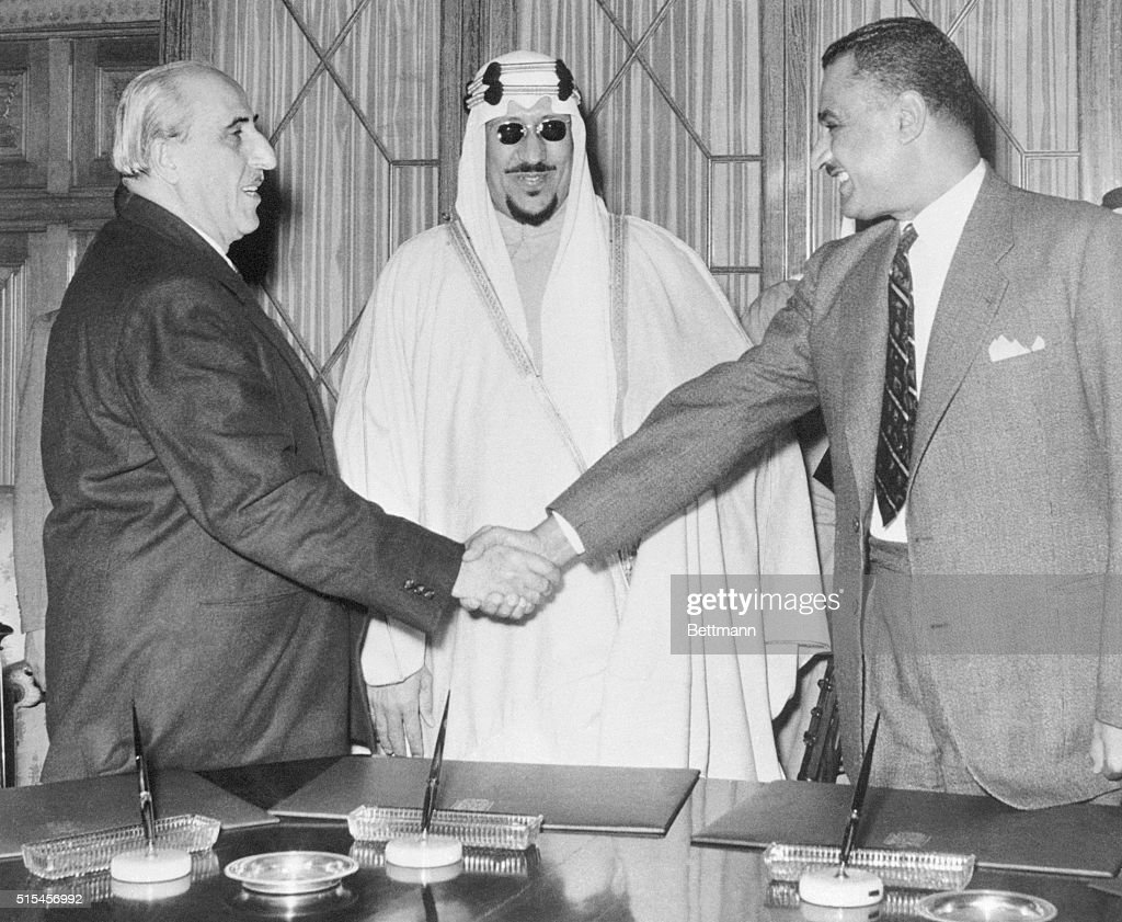 Syrian President Shukry El Kuwatly (left) and Egyptian Premier Gamal Abdel Nasser shake hands, as Saudi Arabia's King Saud looks on smilingly after the signing of the joint communique. The declaration, which climaxed a series of meetings of the Arab States' 'Big Three' here, announced that the three had agreed on a plan to safeguard Arab security and defend the Arab world against 'the danger of Zionist aggression and foreign domination.'