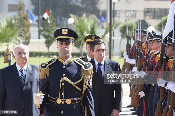 Syrian Prime Minister Naji alOtri and his French counterpart Francois Fillon review an honour guard during a welcoming ceremony for the latter at the...
