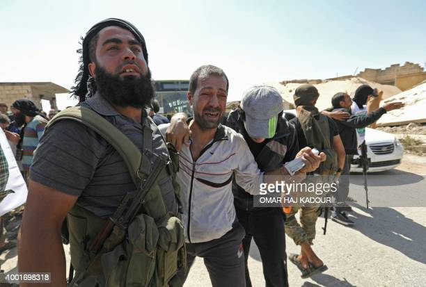 A Syrian prisoner released from a regime jail is surrounded by rebelfighters as he reacts upon his arrival at the alEis crossing point south of...