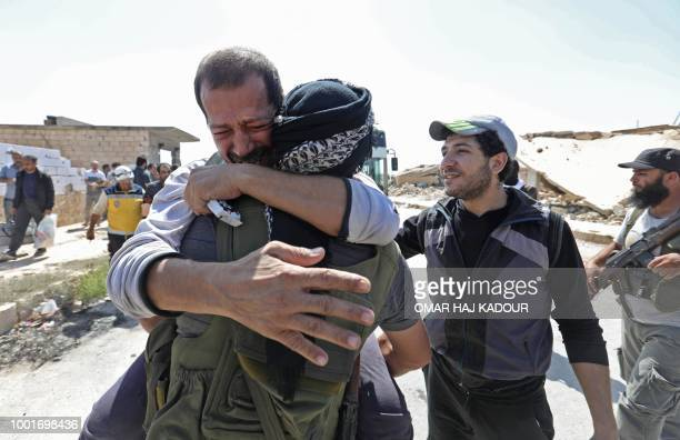 A Syrian prisoner released from a regime jail reacts as he embraces a rebel fighter upon his arrival at the alEis crossing point south of Aleppo on...