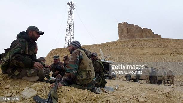 Syrian progovernement forces rest next to the Palmyra citadel on March 26 during a military operation to retake the ancient city from the jihadist...