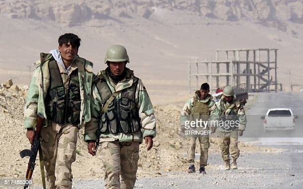 Syrian progovernement forces walk on a road on the outskirts of Palmyra on March 25 during a military operation to retake the ancient city from the...