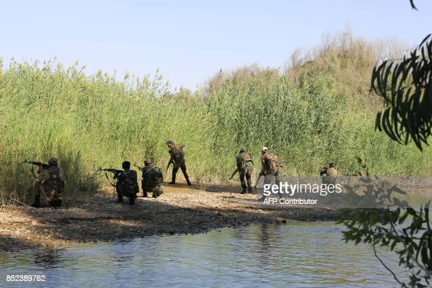 Syrian progovernment fighters are seen in area of the Hawija Qate in the Euphrates river outside the eastern city of Deir Ezzor on September 23 2017...