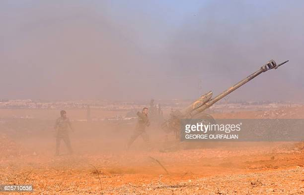 TOPSHOT Syrian progovernment fighters fire a Russian 122mm howitzer gun as they advance in the recently recaptured village of Joubah during an...