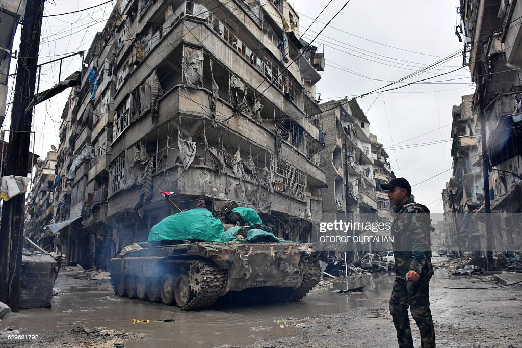 TOPSHOT - Syrian pro-government forces advance in the Jisr al-Haj neighbourhood during the ongoing military operation to retake remaining rebel-held areas in the northern embattled city of Aleppo on December 14, 2016. Shelling and air strikes sent terrified residents running through the streets of Aleppo as a deal to evacuate rebel districts of the city was in danger of falling apart. / AFP / George OURFALIAN